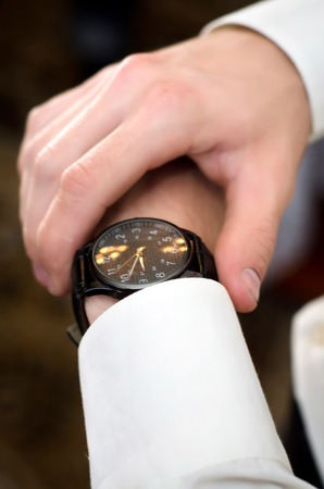 hand cuff: The man in the white shirt watching the time on her clock on the hand closeup