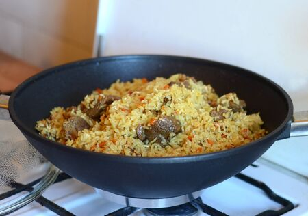 stewing: Delicious pilaf with meat and rice just cooked in a black cauldron on a gas stove