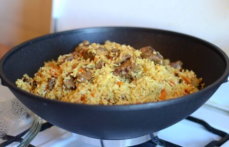 Delicious pilaf with meat and rice just cooked in a black cauldron on a gas stove