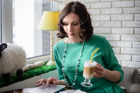 touchpad: Beautiful girl in green dress sitting at the table with coffee in hand and looks at the tablet in sunlight on the background of a white brick wall and windows