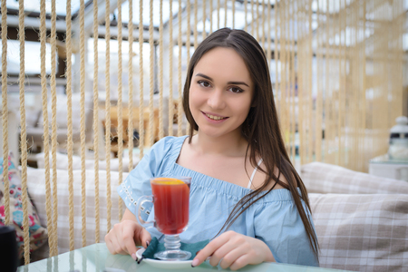 Beautiful girl in a blue blouse with a glass of mulled wine sitting at a table in a cafe