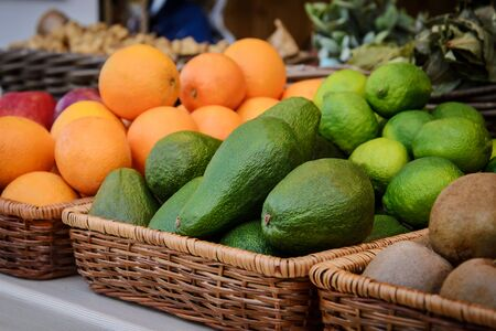 barter: Bright green avocado and other fruits on the counter in a wicker tray Stock Photo
