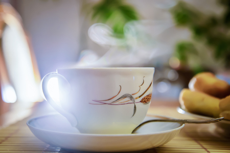 Steam rises over the white teacup with hot tea on the table in the room Stock Photo
