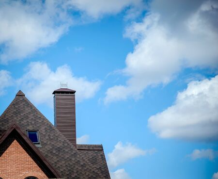 Part tiled brown roof with a chimney on background of blue sky with white clouds