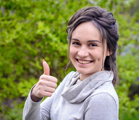 Beautiful smiling girl brown-eyed brown-haired woman in a light gray jacket on a background of green foliage give the thumbs up Stock Photo