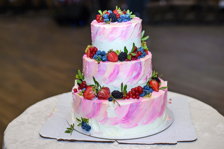 Beautiful delicious three-tiered wedding cake with fresh organic berries: strawberries, currants, blackberries, blueberries and white pink cream Stock Photo