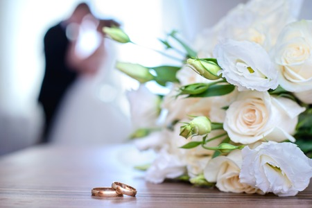 Gold wedding rings and bouquet from white roses on a background of blurred newlyweds 写真素材