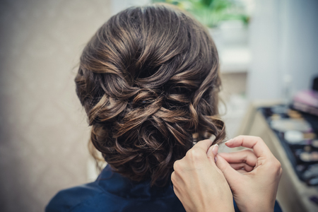 Ręce fryzjera robią fryzurę ślubną z lokami na zbliżenie długich brązowych włosów