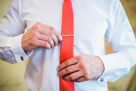 Man in white shirt adjusting his clip on red tie closeup