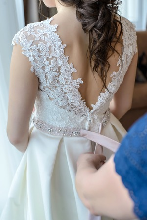 Womens main cravate bel arc rose sur la robe blanche de la mariée dos closeup Banque d'images - 99273020