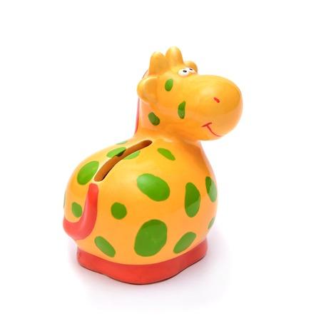 Funny porcelain figurine piggy Bank yellow cow is similar to a giraffe with green spots, isolate on white background