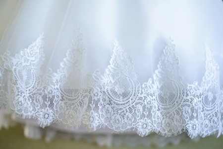 White delicate openwork hem wedding dress closeup