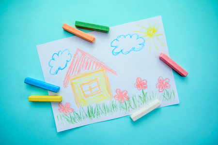 Children's drawing with colored chalks with a house, grass, flowers and clouds on a blue background