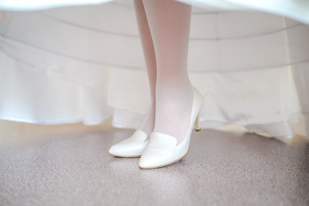 White wedding shoes on the legs of the bride under the dress Stock Photo