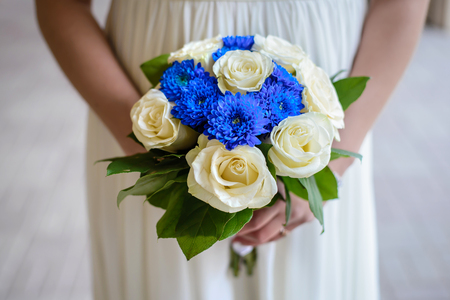 Beautiful wedding bouquet of white roses and blue dahlias in the hands of the bride closeup Reklamní fotografie