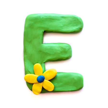 Lettre de pâte à modeler verte E alphabet anglais avec fleur jaune, isoler sur fond blanc Banque d'images