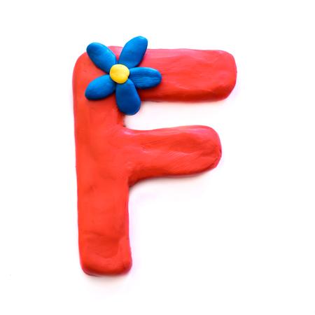 Lettre de pâte à modeler rouge F alphabet anglais avec fleur bleue, isoler sur fond blanc