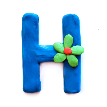Blue plasticine letter H English alphabet with green flower, isolate on white background
