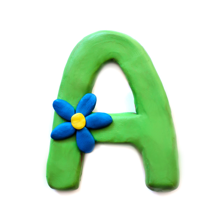 Green plasticine letter A of English alphabet with blue flower, isolate on white background