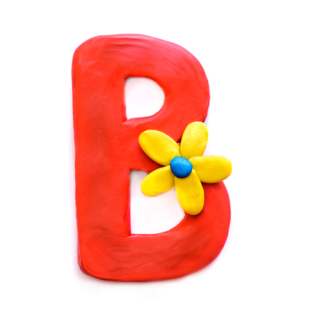 Red clay letter B of the English alphabet with yellow flower, isolate on white background