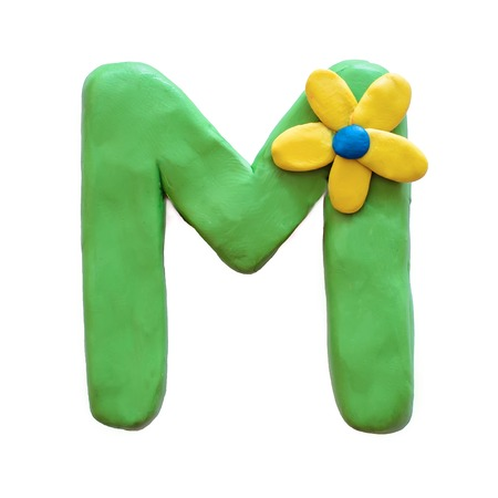 Green plasticine letter M English alphabet with yellow flower, isolate on white background