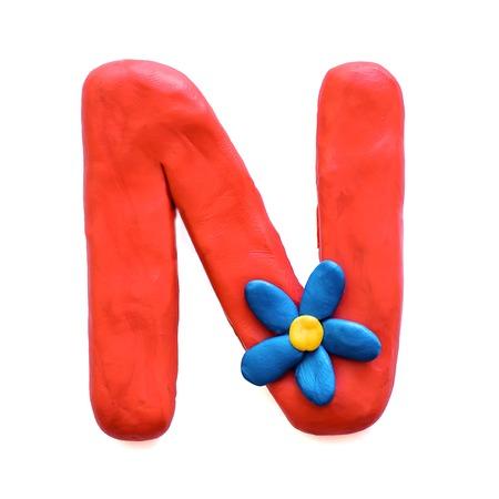 Lettre de pâte à modeler rouge N alphabet anglais avec fleur bleue, isoler sur fond blanc Banque d'images