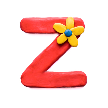 Red plasticine letter Z of English alphabet with yellow flower, isolate on white background