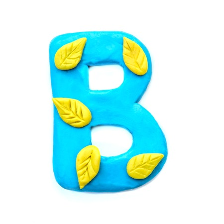 Plasticine light blue letter B of the English alphabet with yellow autumn leaves