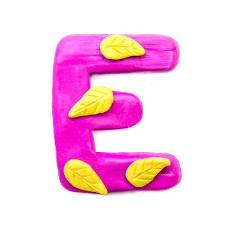 Plasticine purple letter E of the English alphabet with yellow autumn leaves