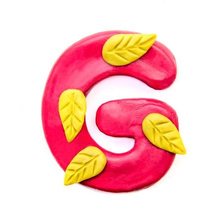 Plasticine handmade crimson letter G of the English alphabet with yellow autumn leaves Stock Photo