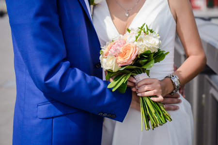 Wedding bouquet of beautiful pink and white roses in the hands of the bride and groom closeup