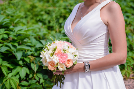 Beautiful wedding bouquet of delicate pink and white roses in the hands of the bride in a white dress closeup