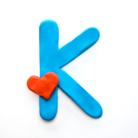 Blue plasticine letter K English alphabet with red heart meaning love on Valentines day, isolate on white background Reklamní fotografie