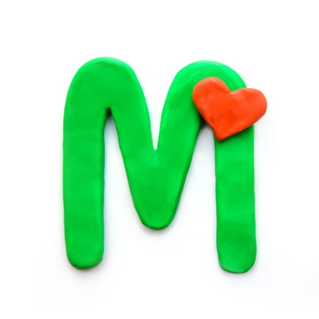 Green plasticine letter M English alphabet with red heart meaning love on Valentines day, isolate on white background