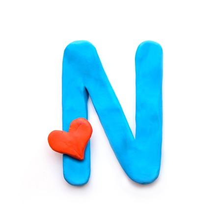 Niebieska plastelina litera N alfabetu angielskiego z czerwonym sercem, co oznacza miłość na Walentynki, wyizoluj na białym tle