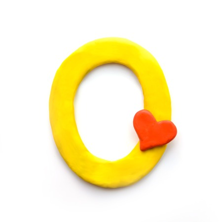 Yellow plasticine letter O English alphabet with red heart meaning love on Valentine's day, isolate on white background Imagens