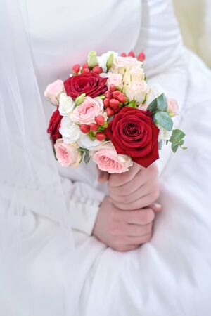 Wedding bouquet of red and pink roses in the hands of the bride closeup Standard-Bild - 125735645