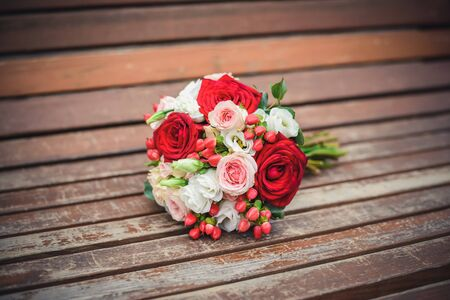 Wedding bouquet of red and pink roses on an old brown wooden bench Standard-Bild - 125735644