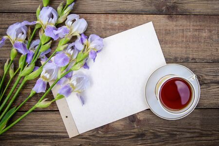 Beautiful purple flowers irises, a sheet of paper and a cup of tea on a wooden rustic background in summer, top view, with copy space Standard-Bild - 125735748