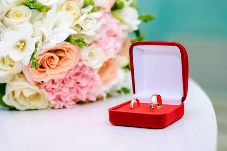 Gold wedding rings in a red box next to the bride's bouquet Standard-Bild - 125735753
