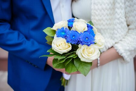 Beautiful wedding bouquet of blue and white roses in the hands of the bride and groom close-up Standard-Bild - 125735763