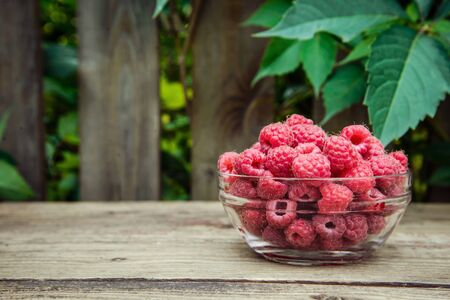 Sweet fresh raspberry in a glass dish on a wooden rustic background with a copy space Standard-Bild - 125735765