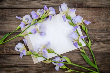 Beautiful purple flowers irises and a sheet of paper on a wooden rustic background in summer, top view, with a copy space Standard-Bild - 125735825