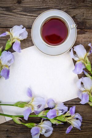 Beautiful purple flowers irises, a sheet of paper and a cup of tea on a wooden rustic background in summer, top view, with copy space Standard-Bild - 125735829