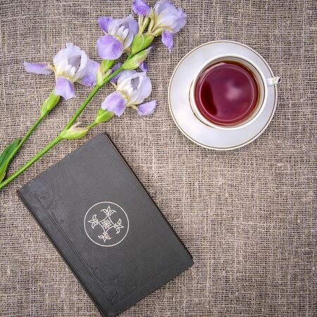 Beautiful purple flowers irises, old book and a cup of tea on a gray canvas background, top view Standard-Bild - 126265810