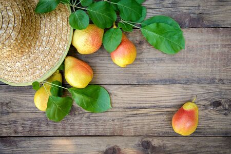 Harvest of ripe yellow-red pears in a wicker dish on a wooden background Standard-Bild - 126265812