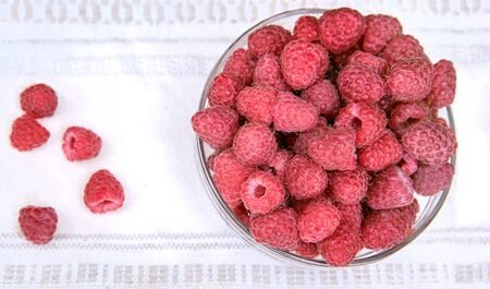 Sweet fresh raspberry in a glass dish on a white textile napkin, top view, with a copy space Standard-Bild - 126265824