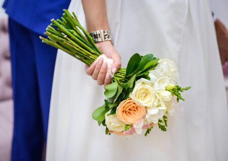 Wedding bouquet of beige roses in the hand of the bride close-up Standard-Bild - 126265829