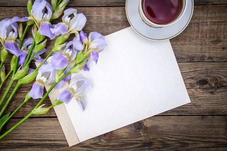 Beautiful purple flowers irises, a sheet of paper and a cup of tea on a wooden rustic background in summer, top view, with copy space Standard-Bild - 127655747