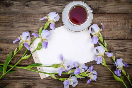 Beautiful purple flowers irises, a sheet of paper and a cup of tea on a wooden rustic background in summer, top view, with copy space Standard-Bild - 127655748